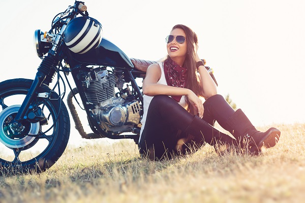 A woman sitting next to her motorcycle