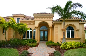 beige florida home with palm tree in front